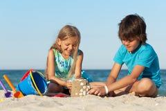 Kinder, die auf dem Strandgebäudesandburg spielen Stockfoto