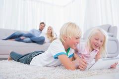 Kinder, die auf dem Teppich unter Verwendung der digitalen Tablette liegen Stockfotos