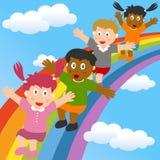 Kinder, die auf den Regenbogen schieben Lizenzfreies Stockfoto