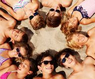 Kinder, die auf den Sand bildet Kreis ihrer Köpfe legen lizenzfreies stockbild