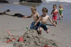 Kinder, die auf den Strand laufen. Stockbilder