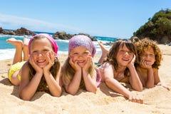 Kinder, die auf den Strand legen. lizenzfreie stockfotografie