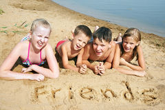 Kinder, die auf den Strand legen Lizenzfreies Stockfoto