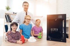 Kinder, die auf der Kamera zusammen mit dem Lehrer und dem Drucker 3d aufwerfen stockfoto