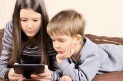 Kinder, die auf der Tablette horizontal spielen Stockfotos