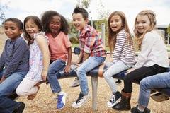 Kinder, die auf einem Karussell in ihrem Schulhof, Seitenansicht sitzen stockbilder