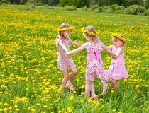 Kinder, die auf einem Löwenzahnfeld spielen lizenzfreie stockfotos