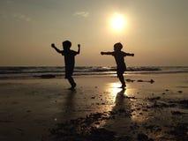 Kinder, die auf einem sandigen Strand spielen Lizenzfreie Stockfotografie
