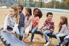 Kinder, die auf einem spinnenden Karussell in ihrem Schulhof sitzen lizenzfreies stockfoto