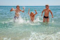 Kinder, die auf einem Strand spielen Lizenzfreie Stockbilder