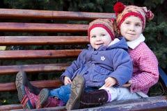Kinder, die auf einer Bank sitzen Lizenzfreie Stockfotografie