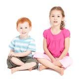 Kinder, die auf Fußboden sitzen Stockfotos