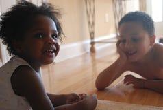 Kinder, die auf Fußboden spielen Stockbild