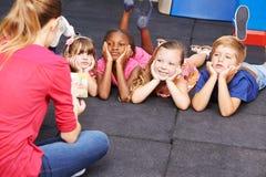 Kinder, die auf Geschichte vom Buch im Kindergarten hören stockfotografie