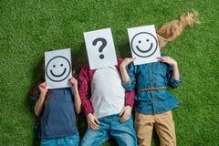 Kinder, die auf Gras liegen und Gesichter mit Bildern bedecken Stockbilder