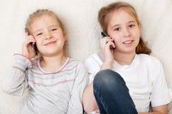 Kinder, die auf Handy sprechen Stockbild