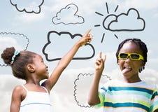 Kinder, die auf Himmel zeigen und mit Wolkenzeichnungen spielen lizenzfreie stockfotos