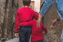 Kinder, die auf ihre Rückseiten auf der Straße gehen lizenzfreies stockfoto