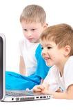 Kinder, die auf Laptopschirm schauen Stockbild
