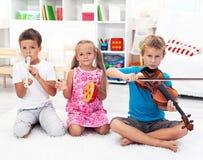 Kinder, die auf Musikinstrumenten spielen Stockbild