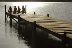 Kinder, die auf Rand der Anlegestelle am See sitzen stockfoto