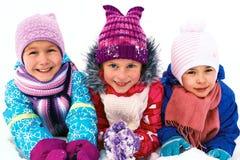 Kinder, die auf Schnee in der Winterzeit spielen Lizenzfreie Stockfotografie