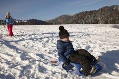 Kinder, die auf Schnee rodeln Stockbilder
