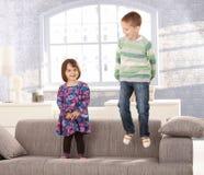 Kinder, die auf Sofa spielen Stockfotos