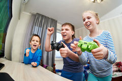 Kinder, die auf Spielkonsole spielen Stockbild