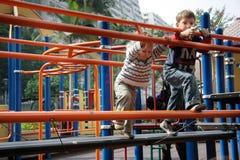 Kinder, die auf Spielplatz spielen Lizenzfreies Stockbild