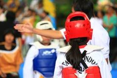 Kinder, die auf Stadium während Taekwondo-Wettbewerbs kämpfen Lizenzfreie Stockbilder