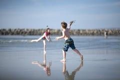 Kinder, die auf Strand des blauen Himmels spielen Stockbild