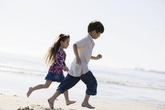 Kinder, die auf Strand laufen Lizenzfreie Stockbilder