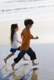 Kinder, die auf Strand laufen Stockbild