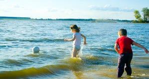 Kinder, die auf Strand spielen Stockfotografie