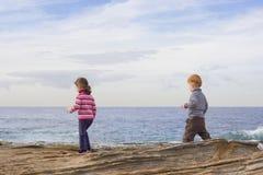 Kinder, die auf Strandfelsen gehen stockfoto