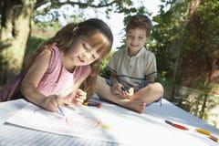 Kinder, die auf Tabelle im Freien zeichnen Stockfotos