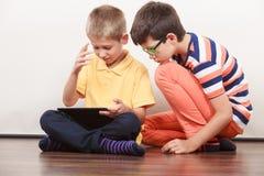 Kinder, die auf Tablette spielen Stockbilder