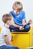 Kinder, die auf Tablette spielen Kinder, die Computer betrachten Stockbild