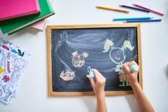 Kinder, die auf Tafel zeichnen Lizenzfreie Stockfotos