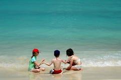 Kinder, die auf tropischem Strand spielen Lizenzfreie Stockfotos