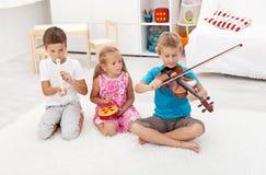Kinder, die auf verschiedenen Musikinstrumenten spielen Lizenzfreie Stockfotos
