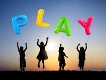 Kinder, die Ballone mit Wort-Spiel halten Stockfoto