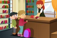 Kinder, die Bücher in der Bibliothek borgen Lizenzfreies Stockfoto