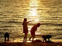Kinder, die bei Sonnenuntergang auf Strand spielen stockfotografie