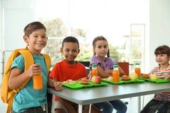 Kinder, die bei Tisch sitzen und gesundes Lebensmittel essen stockfoto