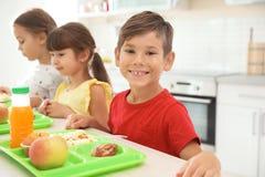 Kinder, die bei Tisch sitzen und gesundes Lebensmittel essen stockbilder