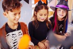 Kinder, die beim Tragen von Halloween-Kostümen im Kindergarten unterhalten glauben stockfotografie