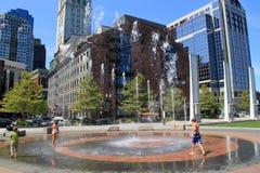 Kinder, die in beschäftigtem Häuserblock Wasserbrunnen pn, Boston, Massachusetts, Sommer, 2013 spielen Stockbilder