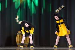Kinder, die in Bienenkostüme tanzen Stockfotografie